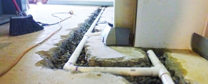 basement floor being excavated and drainage pipe installed for waterproofing project