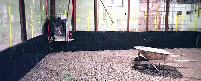 foundation underpinning in the basement of a toronto home with wheel barrow and gravel on the ground