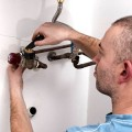 a plumber working on pipes while installing a modern hot water heater inside of a toronto home