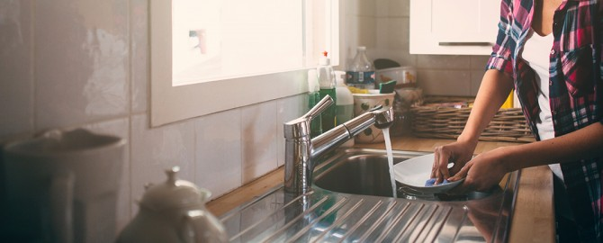 beautiful kitchen with lovely woman cleaning dishes in the kitchen sink