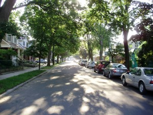 Looking down a street lined with cars in the Danforth village in Toronto