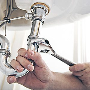 kitchen sink drain being repaired by an acton plumber
