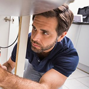 halton hills plumber focusing on repairing the plumbing in the kitchen of a home