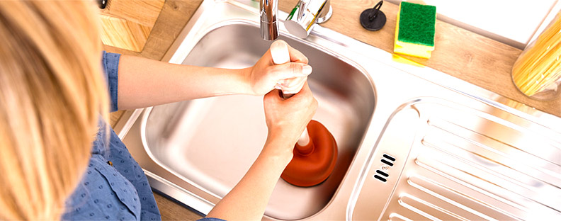 woman that needs her clogged drain repaired, attempting to fix blocked drain with a plunger,